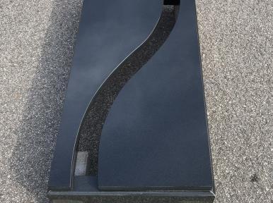 Одиночная надгробная плита из черного гранита, частично закрытая