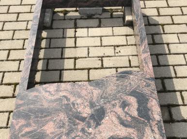 Двойная надгробная плита из красно-коричневого гранита, частично закрытая