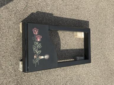 Надгробная плита из черного гранита с рисунком, частично закрытая